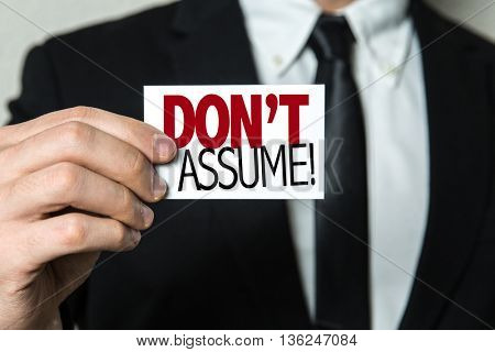 Business man holding a card with the text: Don't Assume