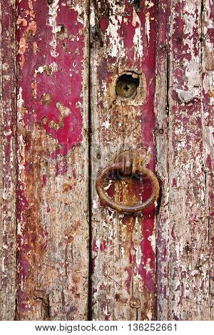 Old grungy wooden door with peeling paint and rough door-handle