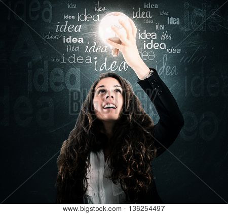 Astonished woman looks at a light bulb