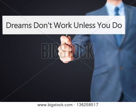 Dreams Don't Work Unless You Do - Businessman Hand Holding Sign