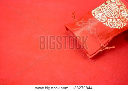 Chinese new year decoration: red fabric packet or ang pow with chinese style pattern and golden coin on red felt fabric