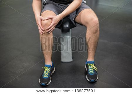 Close-up of man with an injured knee sitting in gym