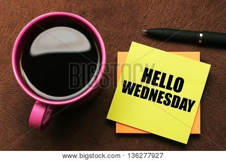 Hello Wednesday - text on sticky note with a pen and cup of coffee