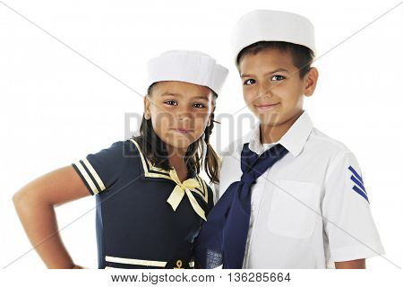 Close-up of a young brother and sister posed together in the sailor outfits.  On a white background.