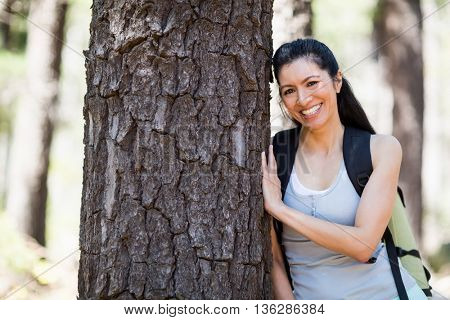 Woman smiling and posing against a tree