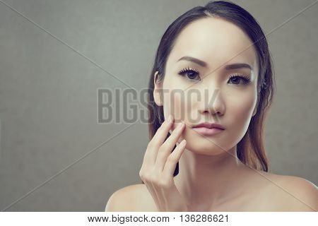 Portrait of pretty Chinese woman touching her face