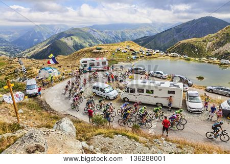 Col de la Croix de Fer, France - 23 July 2015: The peloton riding in a rocky natural environment near the Laitelet Lake at Col de la Croix de Fer in Alps during the stage 20 of Le Tour de France 2015.