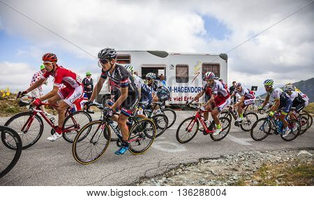 Col de la Croix de Fer, France - 23 July 2015: Group of cyclists (including John Degenkolb of Giant Team and Kenneth Vanbilsen of CofidisTeam) in the peloton riding to the Col de la Croix de Fer in Alps during the stage 20 of Le Tour de France 2015.