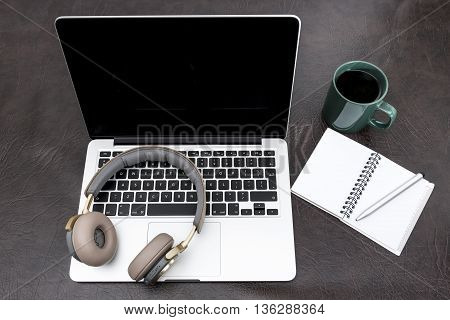 Laptop On A Desk With Headphones, A Notebook And Steaming Coffee