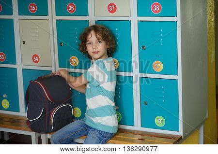 Little schoolboy sitting on the bench near the lockers. His backpack is nearby. The boy looks into the camera with a serious expression. He had curly blond hair and a nice face.
