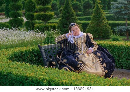 Historical cosplay. Beautiful woman in the similitude of Marguerite of Navarre queen of France ancient dress in the garden near palace