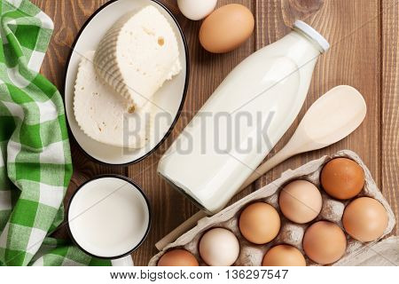 Dairy products on wooden table. Milk, cheese and eggs. Top view