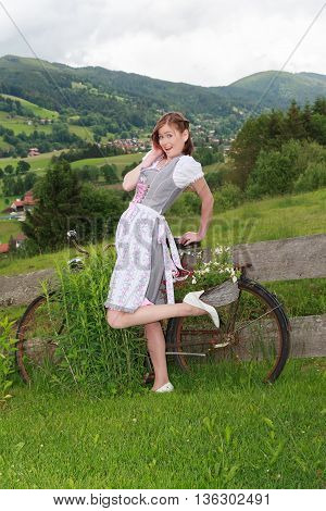 Portrait of a young Bavarian woman in dirndl in amusing pose.