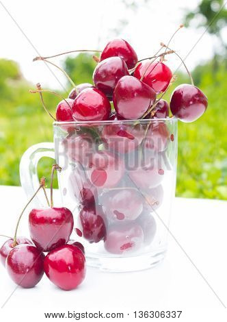 A transparent mug with red fresh juicy cherry berries on a light green and white outdoor background