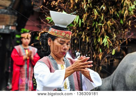 SUMATRA, INDONESIA - 22 MAY 2015 : A Traditional Batak Dancer performing a ceremonial dance in Bolon Simanindo Batak Museum Village. Batak stands for the ethnic people living in the northern part of Sumatra Island of Indonesia.