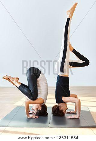 Two Young Women Doing Yoga Asana Crane Pose