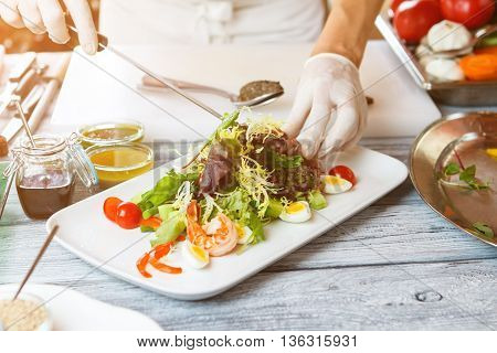 Hands with knife make salad. Salad plate on wooden surface. Salad with frisee and shrimp. Quail eggs and cherry tomatoes.