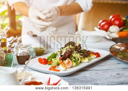Salad on white plate. Man standing near salad plate. Anchovy tapenade and quail eggs. European cuisine at the restaurant.