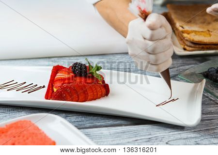 Slices of strawberry on plate. Hand with tool decorates dessert. Liquid chocolate for tasty dessert. Chef makes a flan.