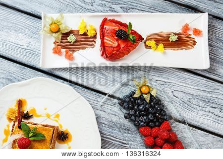 Cake and berries on plates. Blueberry and raspberry. European desserts on restaurant table. Honey cake and strawberry flan.