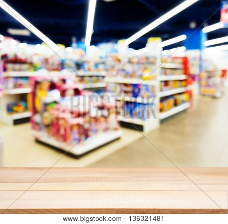 Wooden board empty table in front of blurred background. Perspective light wood table over blur in kids toy store. Mock up for display or montage your product.