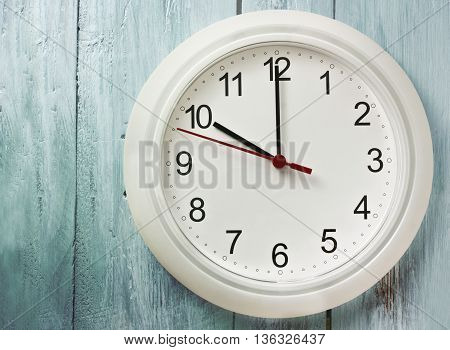 'Beginning of workday' or 'time' concept: a photo of a typical white office clock on a teal blue background with copyspace
