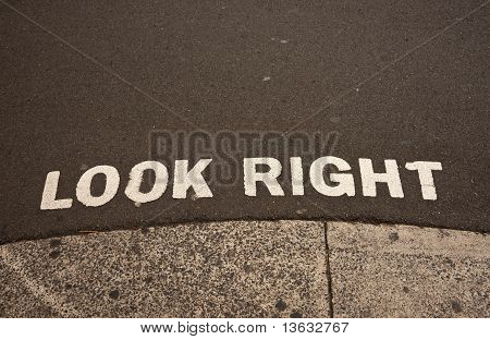 """Look Right"", sign on road edge advising safety for pedestrians."
