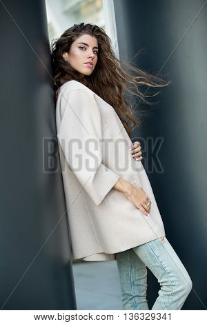 Pretty girl with windblown hair leans on the column outdoors. She wears a cream coat and light ripped jeans. She looks into the camera and holds her hands on the coat. She has rings on the right hand. Photographed from the side. Vertical.