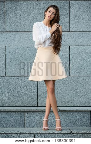 Tender girl with beautiful hairstyle stands with crossed legs on the gray wall background. She wears a white blouse, beige skirt and beige sandals. She holds her hair with the hands. She has rings on the right hand. She looks into the camera with parted l