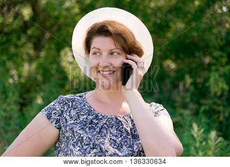 A woman in a hat talking on cell phone outside