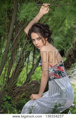 Charming girl in a dress and silver sandal squats on the background of trees. Dress is with silver bottom and flowered top. She holds the branch with her right hand, left hand is on the knees. She looks into the camera. Photographed from the side. Vertica