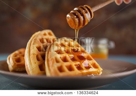 Honey pouring on a fresh waffles. Breakfast with Belgian waffles