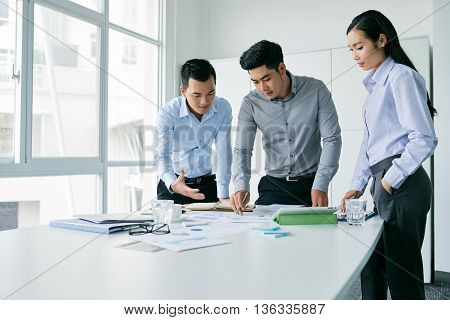 Young Vietnamese business team gathered at table with documents