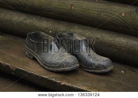 dirty handmade galosh rubbers near wood wall