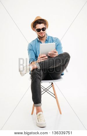 Handsome attractive happy joyful young man using tablet and sitting on the chair isolated on the white background