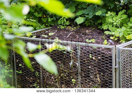 Compost metal bin in green garden at spring