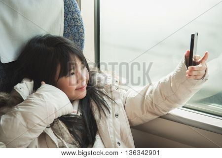 Little asian girl taking selfie picture and sharing social media in a smart phone . She travels on a train