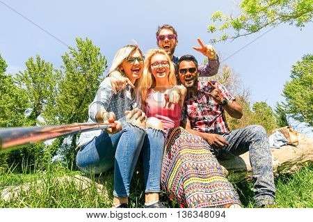 Group of multiracial friends taking selfie with stick sitting on old tree trunk - Mixed race students having fun at green park - Concept of joyful moment on sunny spring day - Bright Vintage filter