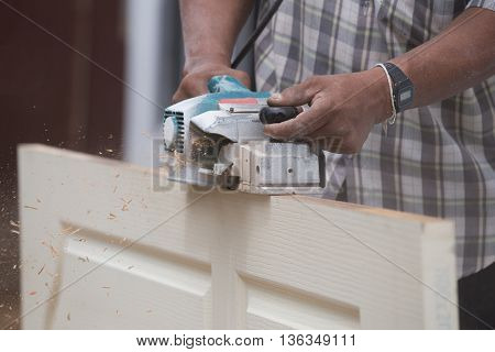 Worker Planing A Wood Of Door With Electric Plane