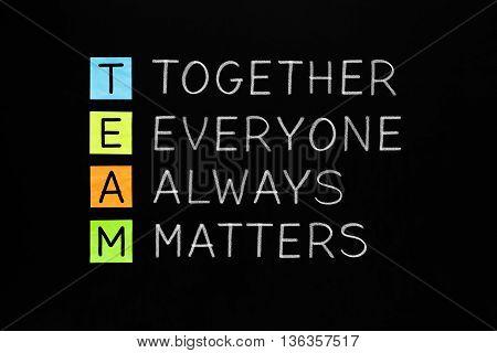 TEAM acronym Together Everyone Always Matters handwritten with white chalk on blackboard. Teamwork concept.
