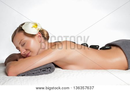 Beauty treatments woman getting spa on a stone therapy hot stone massage. Isolated on white.