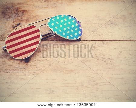 mirror glasses with american flag pattern on wooden background.4th of July concept. Vintage filter effect