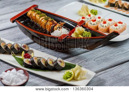 Sushi boat and plates. Different sushi rolls. Cream cheese and fresh tuna. Feast for sushi lovers.
