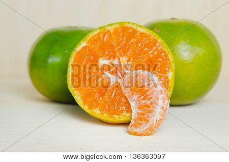 Orange fruit (Other names are Les Oranger sweet orange citrus sinensis Citrus aurantium Citrus maxima Citrus reticulate mandarin orange) with half view isolated on wood background