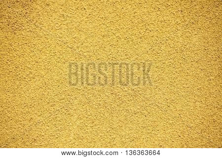 Rugged plaster wall on ochre textured background