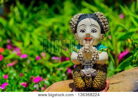 Thai stucco doll Sawasdee in the garden.