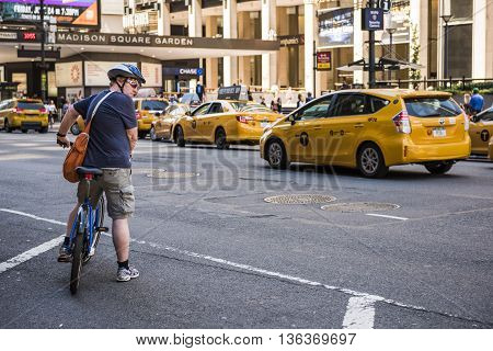New York, USA - June 18, 2016: Man on a bicycle crossing road filled with taxi cabs in Madison Square Garden in New York City