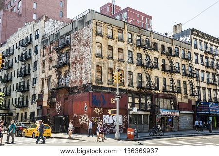New York, USA - June 18, 2016: People walk next to old, rusty building with graffiti in Chinatown in New York City