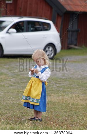 VADDO SWEDEN - JUNE 23 2016: Litte girl wearing traditional costume before the traditional dancing around the the maypole celebrating the Midsummer in Sweden June 23 2016
