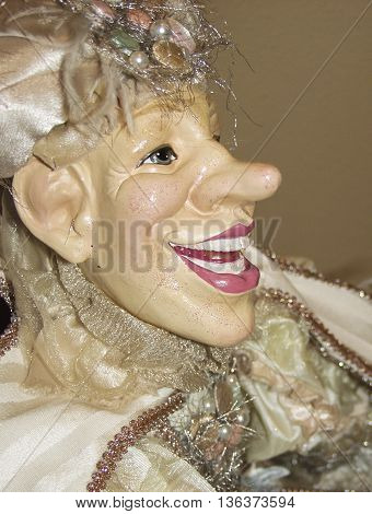 A profile of a porcelain jester doll.